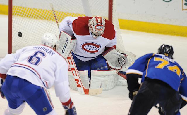 Montreal Canadiens goalie Carey Price, center, blocks a shot by St. Louis Blues' T.J. Oshie (74) as Canadiens' Douglas Murray (6), of Sweden, defends during the second period of an NHL hockey game on Thursday, Dec. 19, 2013, in St. Louis. (AP Photo/Bill Boyce)