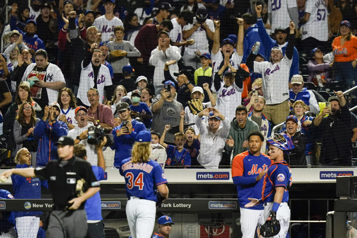 Fans cheer for New York Mets starting pitcher Noah Syndergaard as he walks to the dugout during the first inning in the second baseball game of a doubleheader against the Miami Marlins Tuesday, Sept. 28, 2021, in New York. (AP Photo/Frank Franklin II)