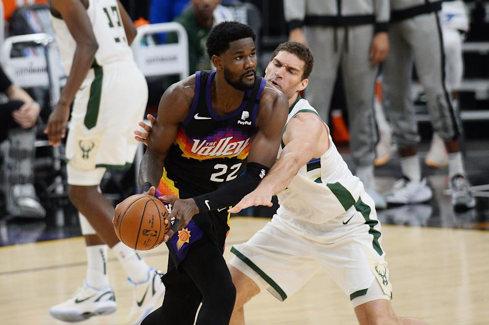 Phoenix Suns center Deandre Ayton (22) looks to pass the ball as Milwaukee Bucks center Brook Lopez (11) defends in the first half during Game 5 of the NBA Finals.