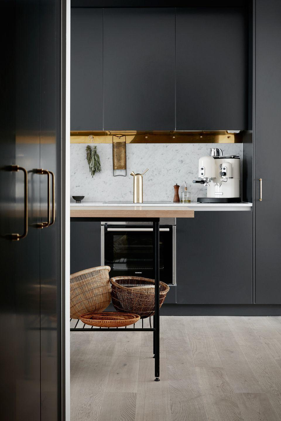 <p>There's nothing sexier than matte black when it comes to kitchen paint colors. Except, that is, when you cover the bottom of the overhead cabinets with a gold mirrored material.</p>