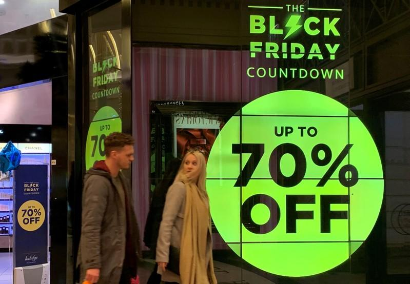 People walk past a sign advertising Black Friday offers at a perfume store in Manchester