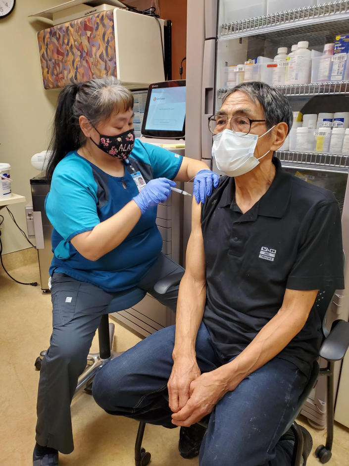 """In this photo provided by Norton Sound Health Corp., is nurse LaVerne Saccheus providing a vaccination to Unalakleet elder Joseph """"Nupid"""" Katchatag in Unalakleet, Alaska, on Dec. 23, 2020. Alaska's highest vaccination rates among those 16 or older have been in some of its remotest, hardest-to-access communities, where the toll of past flu or tuberculosis outbreaks hasn't been forgotten. (Carol Charles/Norton Sound Health Corp. via AP)"""