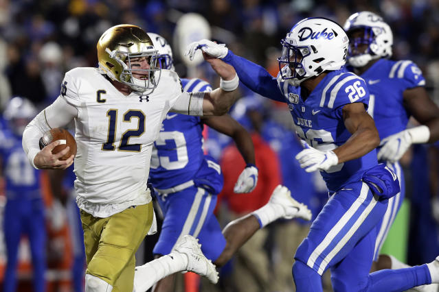 Notre Dame quarterback Ian Book (12) runs the ball while Duke safety Michael Carter II (26) chases during the first half of an NCAA college football game in Durham, N.C., Saturday, Nov. 9, 2019. (AP Photo/Gerry Broome)