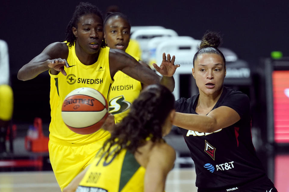 Las Vegas Aces guard Kayla McBride passes the ball after getting around Seattle Storm forward Natasha Howard (6) during the first half of Game 1 of basketball's WNBA Finals Friday, Oct. 2, 2020, in Bradenton, Fla. (AP Photo/Chris O'Meara)