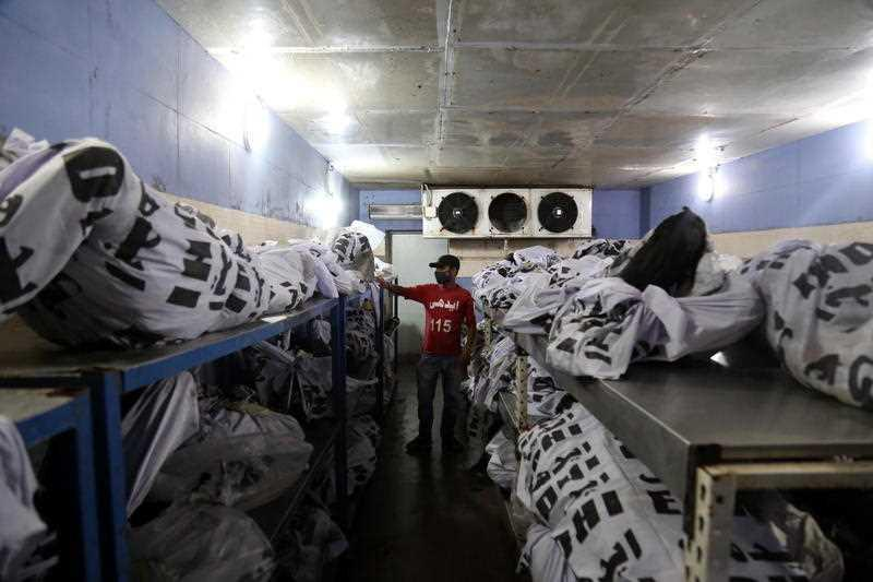 A rescue worker checks bodies of the victims the day after a passenger plane of state run Pakistan International Airlines crashed in a residential area, at a mortuary in Karachi, Pakistan.