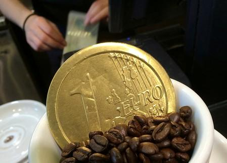 An employee uses a cash till behind a chocolate shaped one Euro coin at a cafe in central London