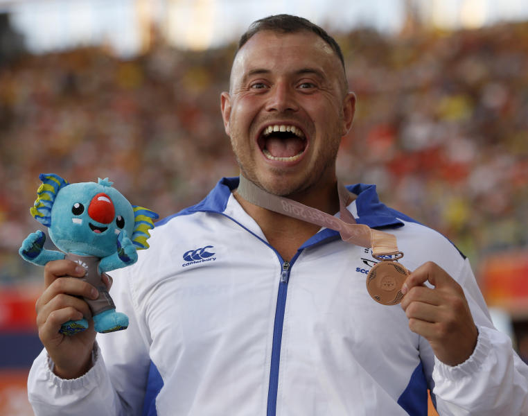 FILE - In this April 8, 2018, file photo, men's hammer throw bronze medalist Mark Dry, of Scotland, reacts on the podium at the Carrara Stadium during the Commonwealth Games on the Gold Coast, Australia. There have been a few high-profile names in track and field making a mess of what is supposed to be a simple process of letting drug testers know where they will be for one hour each day. Dry is serving a four-year doping suspension in a case that came out of a whereabouts violation. (AP Photo/Mark Schiefelbein, File)