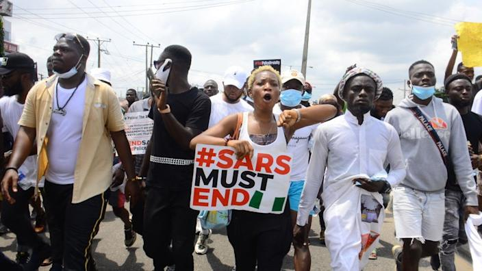 Youths of ENDSARS protesters display their placards in a crowd in support of the ongoing protest against the harassment, killings and brutality of The Nigerian Police Force Unit called Special Anti-Robbery Squad (SARS) at Allen Roundabout in Ikeja, on October 13, 2020.