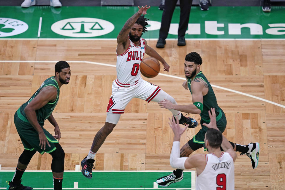 Chicago Bulls guard Coby White, center, passes the ball to Nikola Vucevic (9) while pressured by Boston Celtics forward Jayson Tatum, right, and center Tristan Thompson, left, during the first half of an NBA basketball game, Monday, April 19, 2021, in Boston. (AP Photo/Charles Krupa)