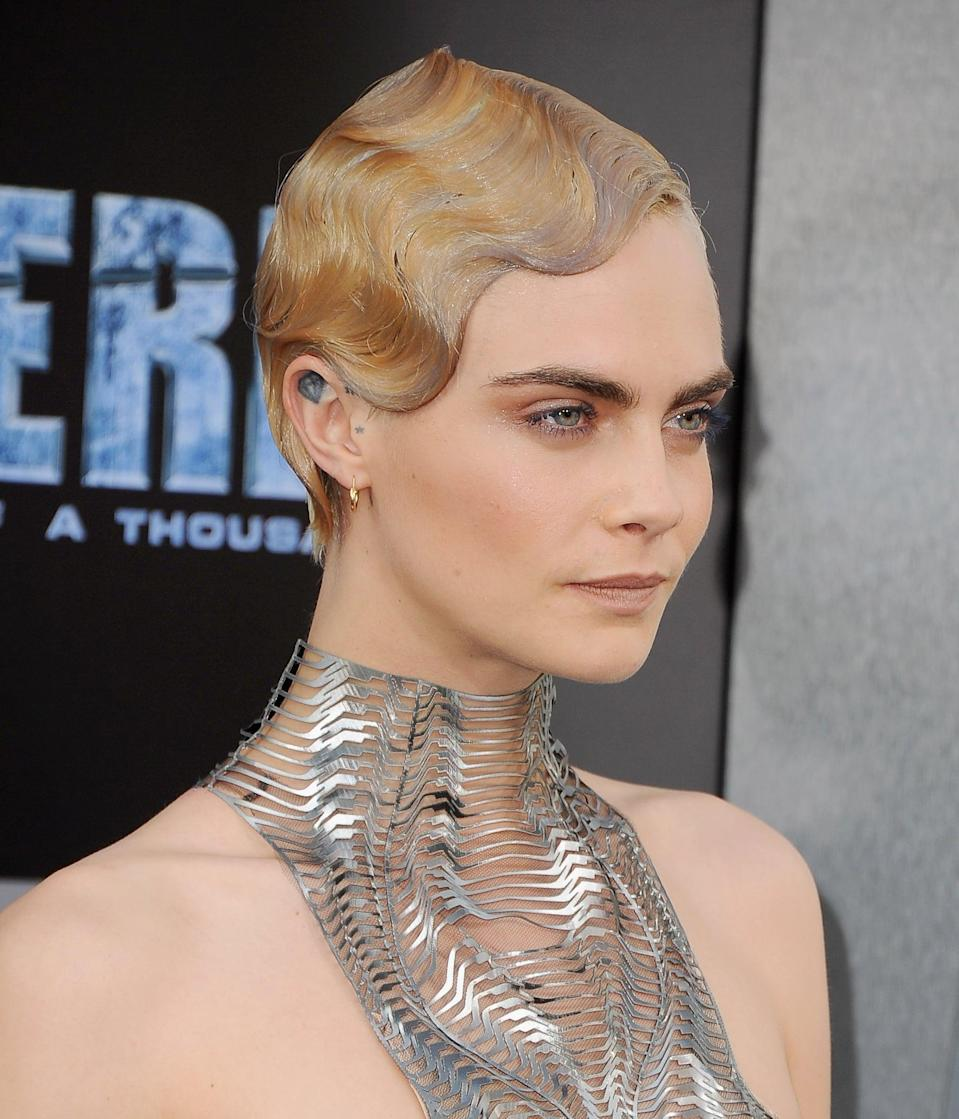 """<p>These finger waves were actually a hair piece: <a href=""""https://www.youtube.com/watch?v=UyVjvLqfthM"""" class=""""link rapid-noclick-resp"""" rel=""""nofollow noopener"""" target=""""_blank"""" data-ylk=""""slk:Roszak added a half wig"""">Roszak added a half wig</a> to one side of Delevinge's hair and used a purple shampoo to give the hair a greyish tone that echoed the color of her silver dress and taupe makeup. </p>"""