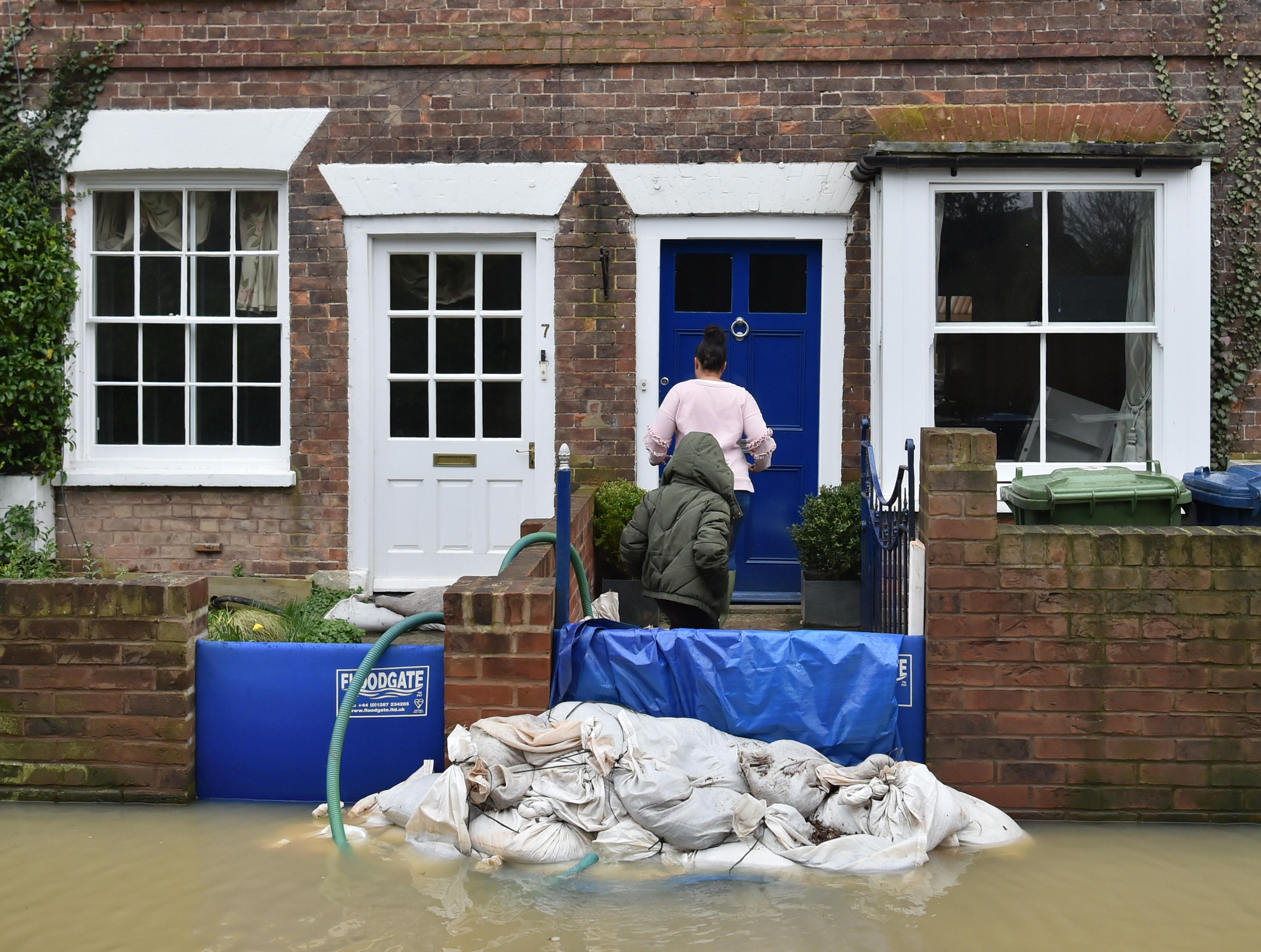 A woman and child enter a cottage in Gloucester Road in Tewkesbury, Gloucestershire, as pumps and flood barriers help to keep the water from flooding the properties, following the aftermath of Storm Dennis.