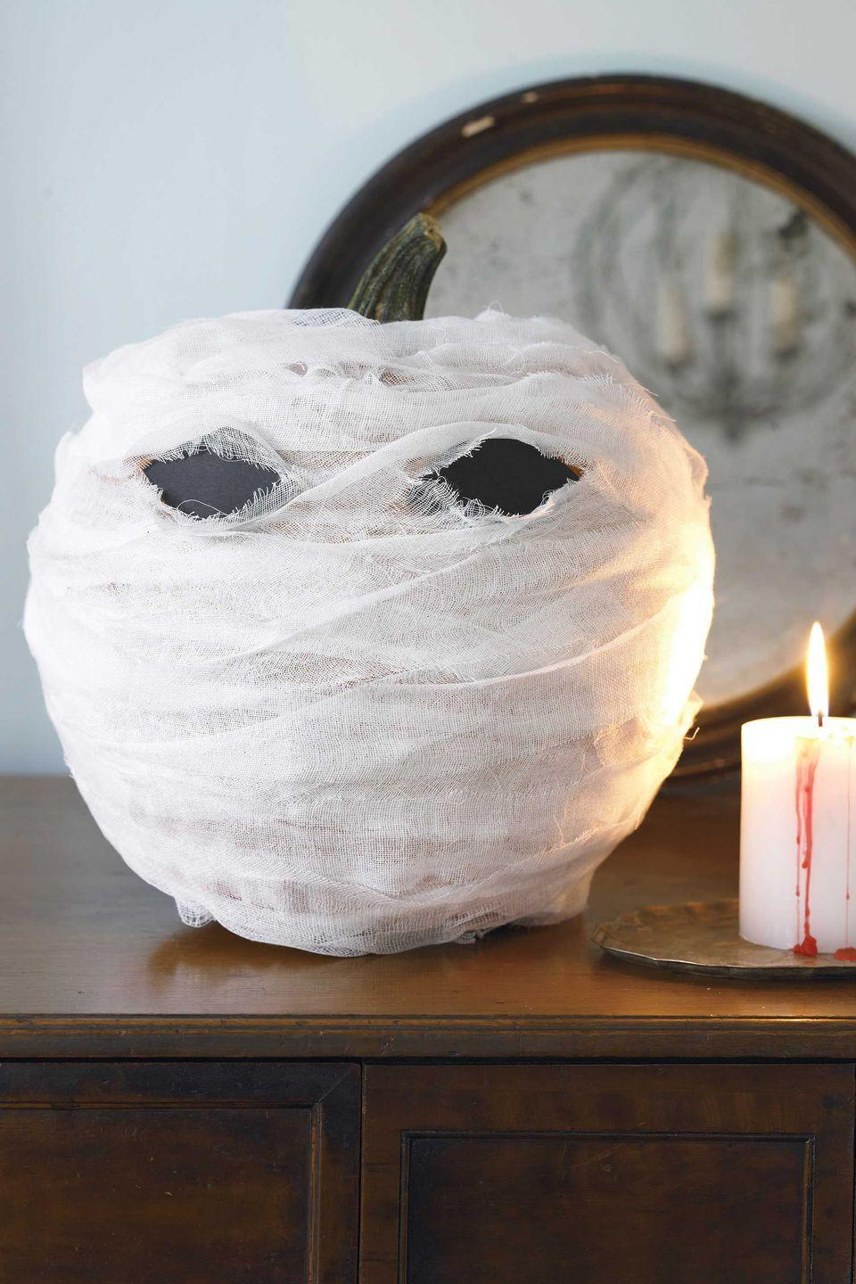 """<p>Wrap a pumpkin in cheesecloth to create an ominous-looking mummy's head. Black construction-paper eyes add to the eerie image.</p><p><strong><em><a href=""""https://www.womansday.com/home/crafts-projects/how-to/a5999/craft-project-menacing-mummy-123881/"""" rel=""""nofollow noopener"""" target=""""_blank"""" data-ylk=""""slk:Get the Menacing Mummy tutorial."""" class=""""link rapid-noclick-resp"""">Get the Menacing Mummy tutorial.</a></em></strong></p>"""
