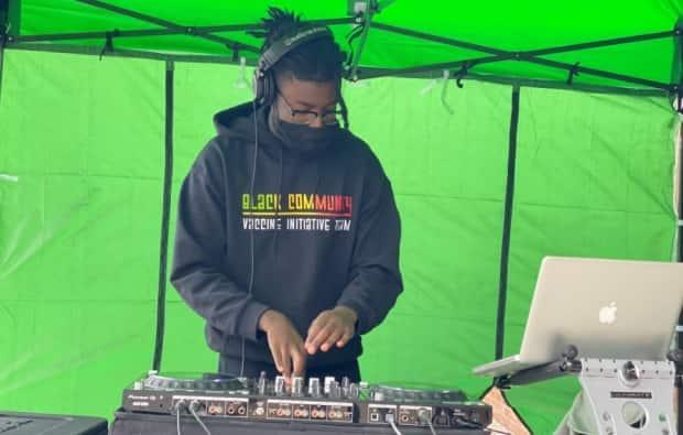 A DJ performs at a pop-up clinic run by the Jamaican Canadian Association to entertain people waiting in the long line to get a COVID-19 vaccine.
