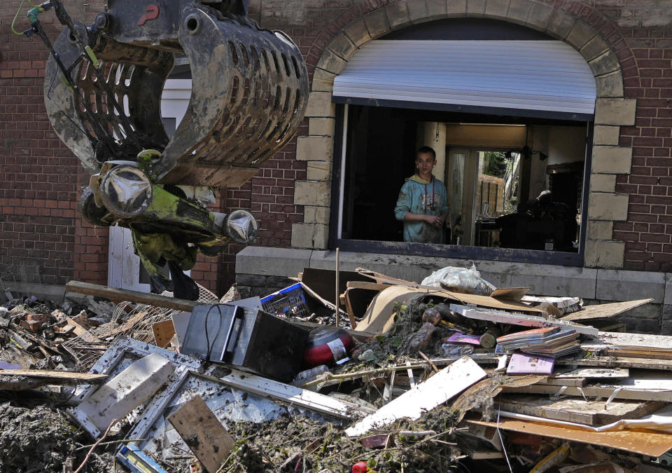 A resident watches from his window as a crane takes away damaged personal belongings after flooding in Drolenval, Belgium, Saturday, July 17, 2021. The Walloon government, has announced a 2 billion euro plan for reconstruction in the storm hit region but money alone won't cover for all the losses suffered by the area. For many residents the trauma they experienced will forever stay in their minds. (AP Photo/Virginia Mayo)