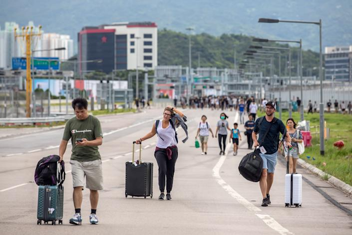Travelers walk with their luggage along a road towards the Hong Kong International Airport during a protest in Hong Kong, China, on Sunday, Sept. 1, 2019. | Paul Yeung/Bloomberg via Getty Images