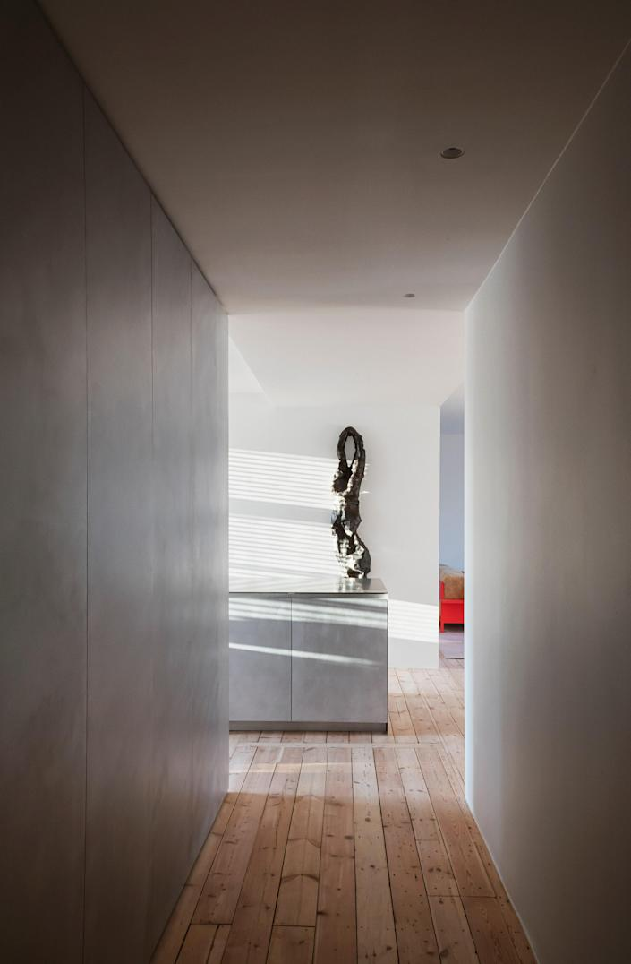 In the entry hall, as throughout the apartment, Thulstrup stripped the existing pine floors and installed brushed-aluminum storage from his modular system for Reform; the wall-mounted artwork is by Carl Emil Jacobsen.