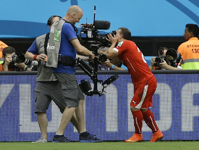 Switzerland's Xherdan Shaqiri kisses a TV camera as he celebrates after scoring the opening goal during the group E World Cup soccer match between Honduras and Switzerland at the Arena da Amazonia in Manaus, Brazil, Wednesday, June 25, 2014. (AP Photo/Kirsty Wigglesworth)