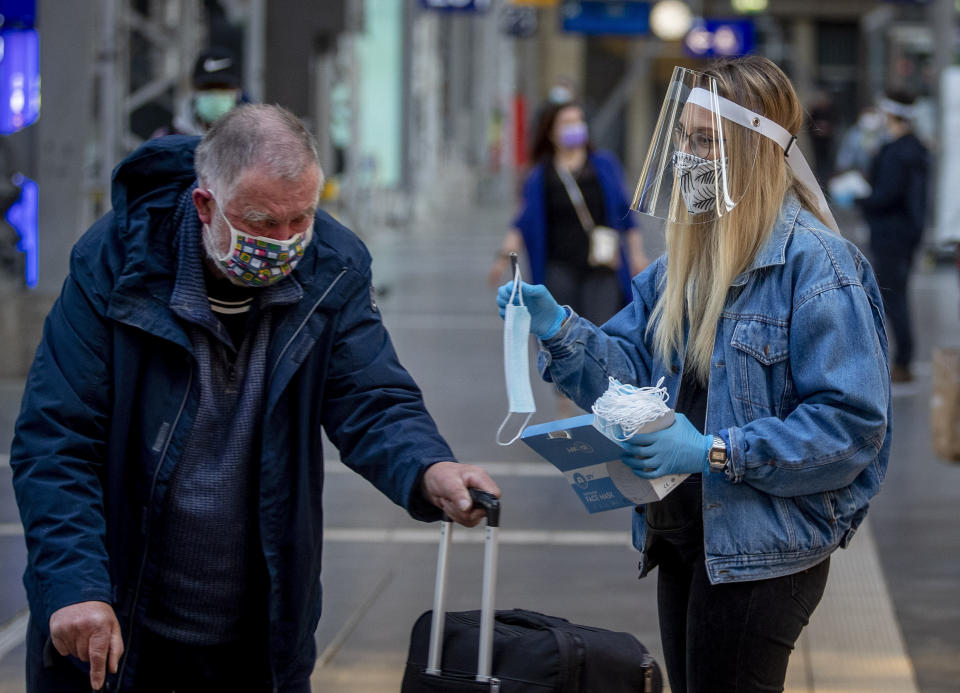 FILE - In this April 27, 2020 file photo, a woman working for the regional public transport company offers a face mask to an elderly man in the main train station in Frankfurt, Germany. More than 50,000 people have died after contracting COVID-19 in Germany, a number that has risen swiftly over recent weeks as the country has struggled to bring down infection figures. (AP Photo/Michael Probst, File)
