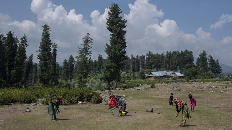 A group of girls play cricket during break.