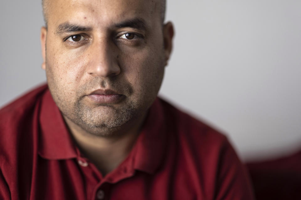 """Afghanistan's Abdul Wali poses in his apartment in Strasbourg, eastern France, Sunday, Sept. 4, 2021. Wali took the last bus out of a huge makeshift migrant camp in the northern French port of Calais. His government bus took him to Strasbourg. """"Now, I'm so happy to be here,"""" he said. """"You're not scared at night"""" like in the migrant camp nicknamed The Jungle. """"You have your job. You have your work, you come back home. You pay your rent. You are a normal person."""" (AP Photo/Jean-Francois Badias)"""