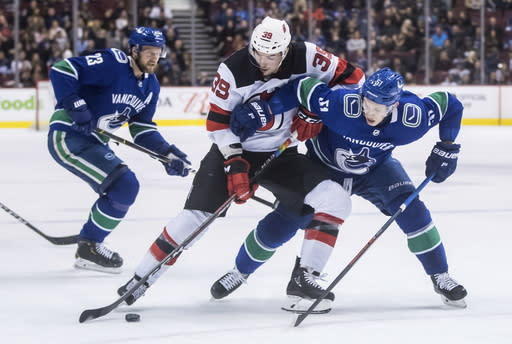 New Jersey Devils' Kurtis Gabriel (39) and Vancouver Canucks' Troy Stecher (51) vie for the puck during the first period of an NHL hockey game Friday, March 15, 2019, in Vancouver, British Columbia. (Darryl Dyck/The Canadian Press via AP)