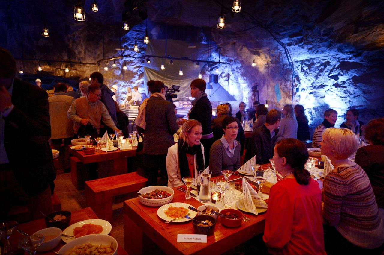 "Customers having dinner at Muru Pop Down -restaurant at Tytyri mine in Lohja, Finland on Monday Sept. 10 2012. The award-winning chef, Niklas Ekblom, is opening a new restaurant in Finland that turns the idea of ""pop-up"" eateries upside-down: it's located 80 meters (260 feet) underground. Discerning food lovers are being served salted salmon, veal tenderloin snails cooked in Pernod, and apple crumble in the ""pop-down"" restaurant in a limestone mine in the small, southern town of Lohja, 60 kilometers (40 miles) west of Helsinki. A four-course evening meal costs 128 euro ($160), including drinks and transportation down to the mine and back up. (AP Photo/Lehtikuva, Antti Aimo-Koivisto) FINLAND OUT"