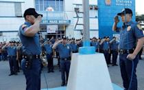 Policemen take part in a flag-raising ceremony at the grounds of Station 6, Batasan Police Station, in Quezon City, Metro Manila, Philippines December 4, 2017. REUTERS/Erik De Castro