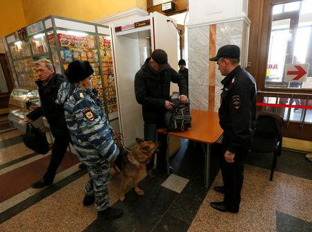 Russian police officers check a passenger at a railway station following the St. Petersburg metro blast that took place on April 3, in Krasnoyarsk