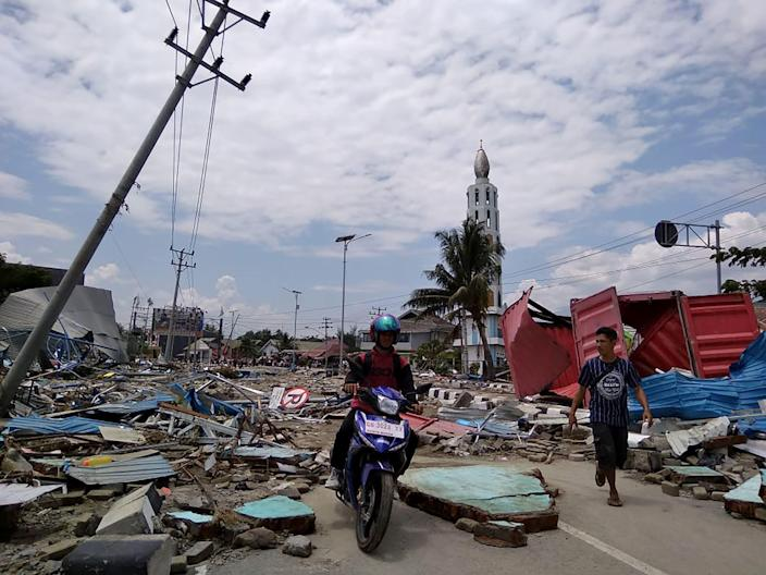 <p>Residents make their way along a street full of debris after an earthquake and tsunami hit Palu, on Sulawesi island on Sept. 29, 2018. (Photo: Muhammad Rifki/AFP/Getty Images) </p>