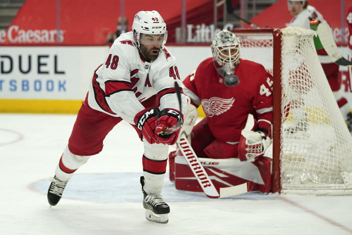 Carolina Hurricanes left wing Jordan Martinook (48) tries to knock down the puck on a pass against the Detroit Red Wings in the third period of an NHL hockey game Sunday, March 14, 2021, in Detroit. (AP Photo/Paul Sancya)