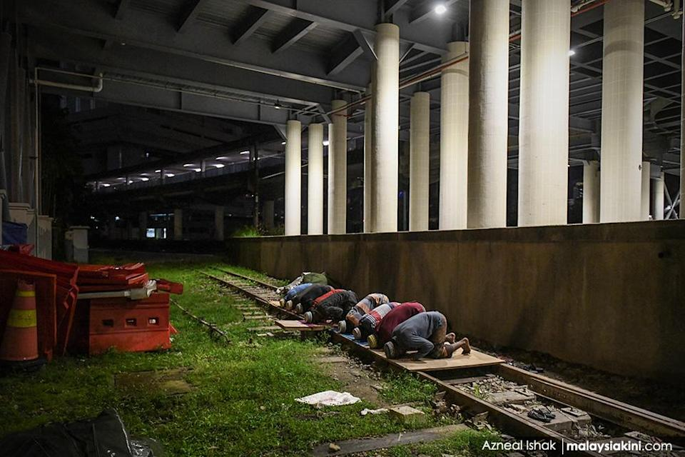 Foreign workers perform tarawih prayers at an LRT rail as Muslims mark Ramadan while coping with the Covid-19 pandemic in Kuala Lumpur on Apr 29, 2020.