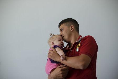 Rogerio dos Santos, 20, holds his daughter, 4-month-old Heloa Vitoria, who was born with microcephaly, at Pedro I Hospital in Campina Grande, Brazil February 18, 2016. REUTERS/Ricardo Moraes
