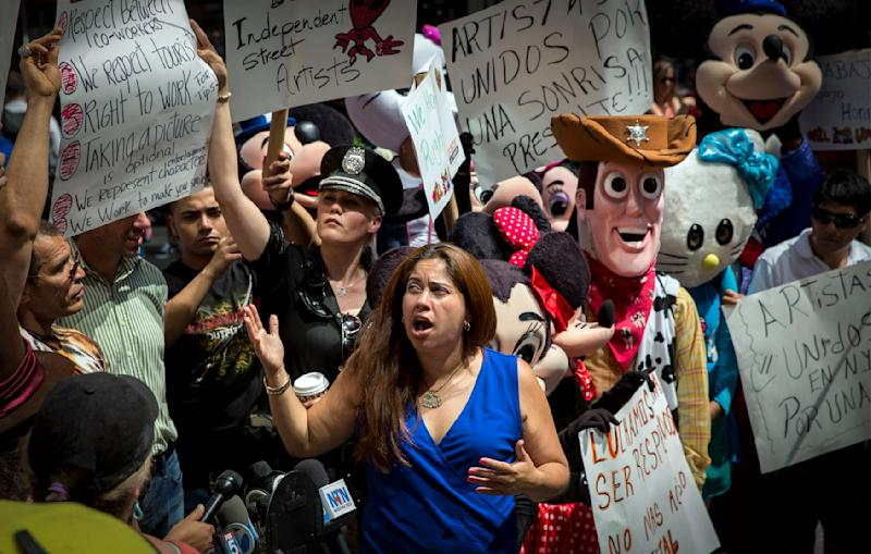 Lucia Gomez of La Fuente, a not-for-profit organization that brings together organized labor, speaks on behalf of Costumed Characters during a rally in support of organizing in New York's Times Square