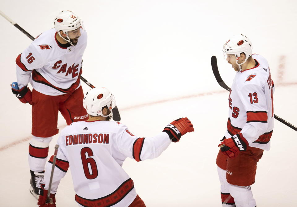 Carolina Hurricanes left wing Warren Foegele (13) celebrates his goal with teammates defenceman Joel Edmundson (6) and center Vincent Trocheck (16) during third period NHL Eastern Conference Stanley Cup playoff action in Toronto on Tuesday, Aug. 4, 2020. (Frank Gunn/The Canadian Press via AP)