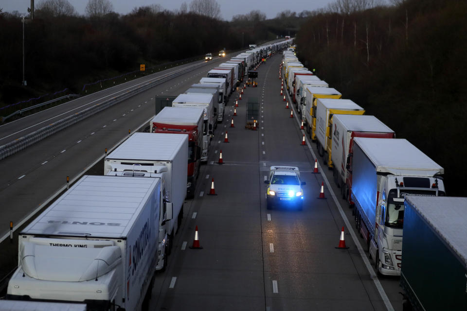 Trucks are parked up on the M20, part of Operation Stack in Ashford, Kent, England, Friday, Dec. 25, 2020. Thousands wait to resume their journey across The Channel after the borders with France reopened. Trucks inched slowly past checkpoints in Dover and headed across the Channel to Calais on Thursday after France partially reopened its borders following a scare over a rapidly spreading new virus variant. (AP Photo/Kirsty Wigglesworth)