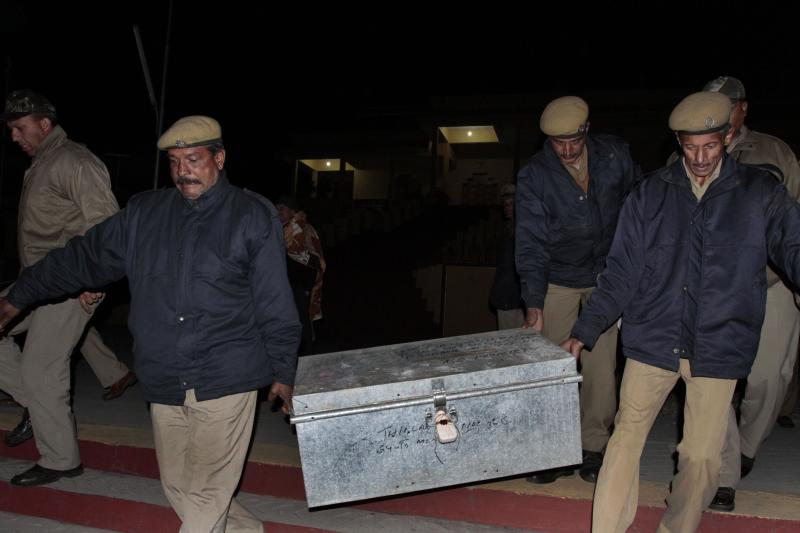 In this Friday, Jan. 28, 2011 photo, policemen carry a metal box containing money from the Gyuto monastery, the home of Ugyen Thinley Dorje, the 17th Karmapa, in Dharmsala, India. Indian authorities have begun investigation into nearly $777,000 that had been found in the northern Indian monastery, the headquarters of Buddhism's third most important Tibetan leader, D.S. Minhas, director general of police in the northern Indian state of Himachal Pradesh said Saturday. (AP Photo/Ashwini Bhatia)