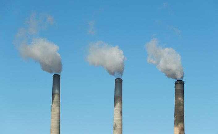 Emissions rise out of three large smokestacks of a coal-fired plant in Utah. A new study suggests the systemic changes scientists say are necessary to avoid the worst effects of warming temperatures willnot be done by corporations alone. (Photo: George Frey/Getty Images)