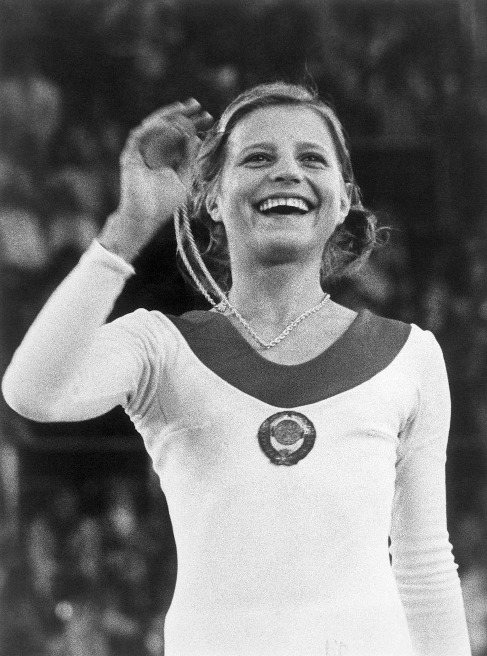 """<p>At just 17 years old, Olga Korbut dominated the podium with four medal wins at the 1972 Munich Olympics. The athlete who competed for the Soviet Union became one of the biggest names in gymnastics thanks to her artistic floor routines and daring stunts—like the <a href=""""https://www.nydailynews.com/sports/olympics-2012/korbut-flip-move-dangerous-today-olympic-gymnasts-aren-allowed-attempt-article-1.1134730"""" rel=""""nofollow noopener"""" target=""""_blank"""" data-ylk=""""slk:Korbut Flip"""" class=""""link rapid-noclick-resp"""">Korbut Flip</a>, which is now banned from competition. </p>"""