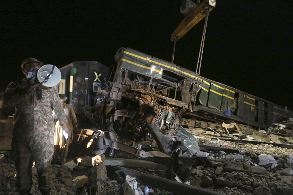 Soldiers and railway workers remove wreckage to clear the track at the site of a train collision in the Ghotki district, southern Pakistan, late Monday, June 7, 2021. An express train barreled into another that had derailed in Pakistan before dawn Monday, killing dozens of passengers, authorities said. More than 100 were injured, and rescuers and villagers worked throughout the day to search crumpled cars for survivors and the dead. (AP Photo/Fareed Khan)
