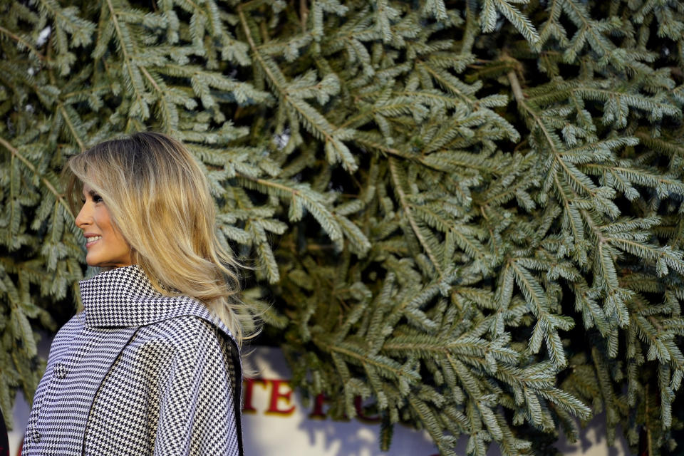 First lady Melania Trump stands next to the 2020 Official White House Christmas tree as it is presented on the North Portico of the White House, Monday, Nov. 23, 2020, in Washington. (AP Photo/Andrew Harnik)