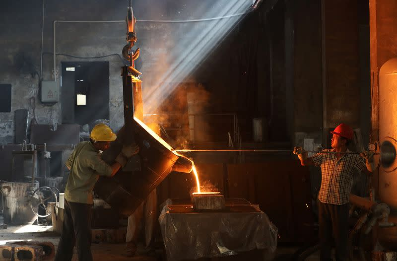 Workers pour molten iron into a mould at a workshop in Hangzhou, Jiangsu
