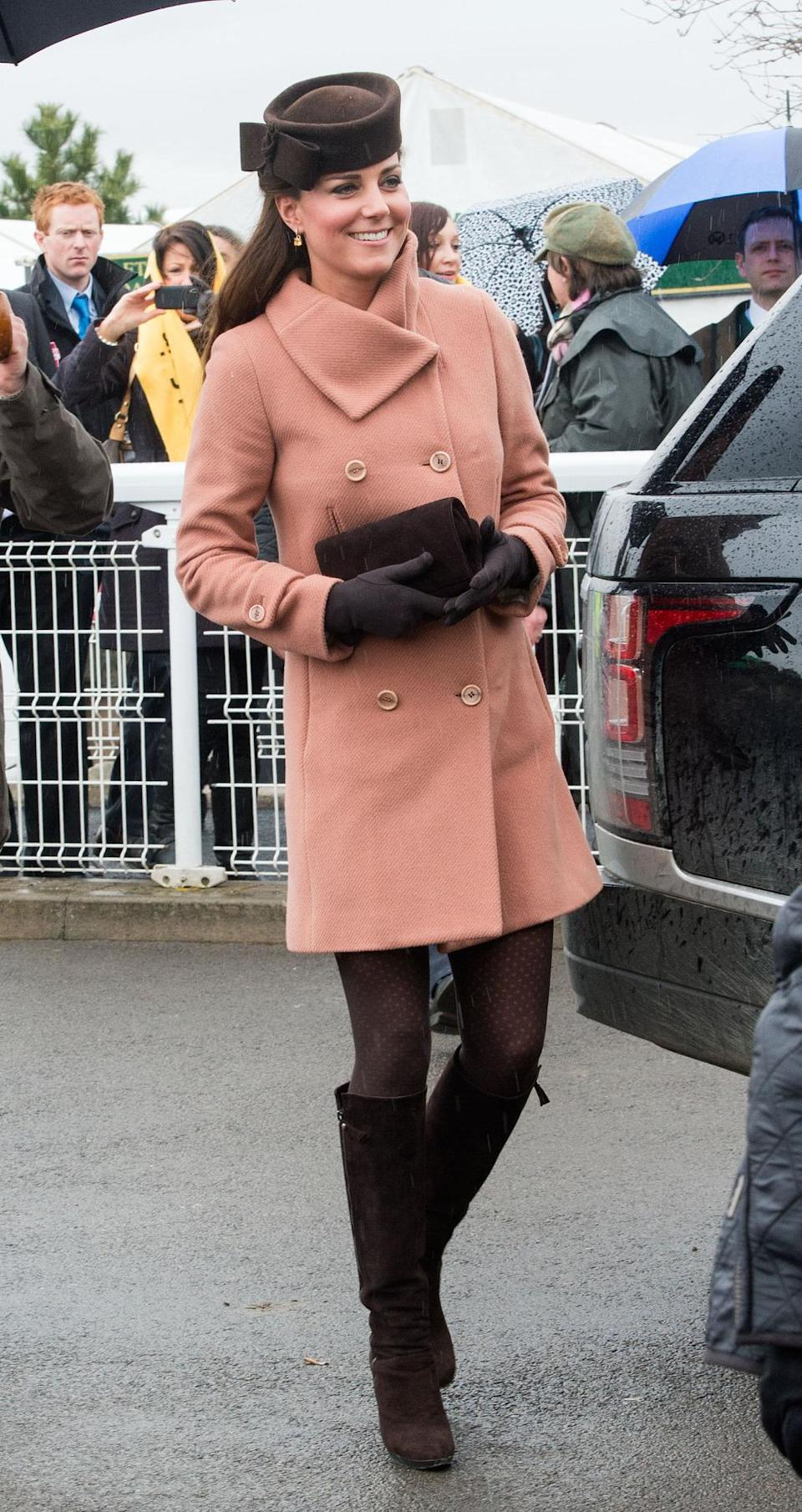 <p>Kate wrapped up at the Cheltenham Festival in a nude coat by Joseph. The Duchess teamed the look with a brown Lock & Co hat and knee high Stuart Weitzman boots. </p><p><i>[Photo: PA]</i></p>