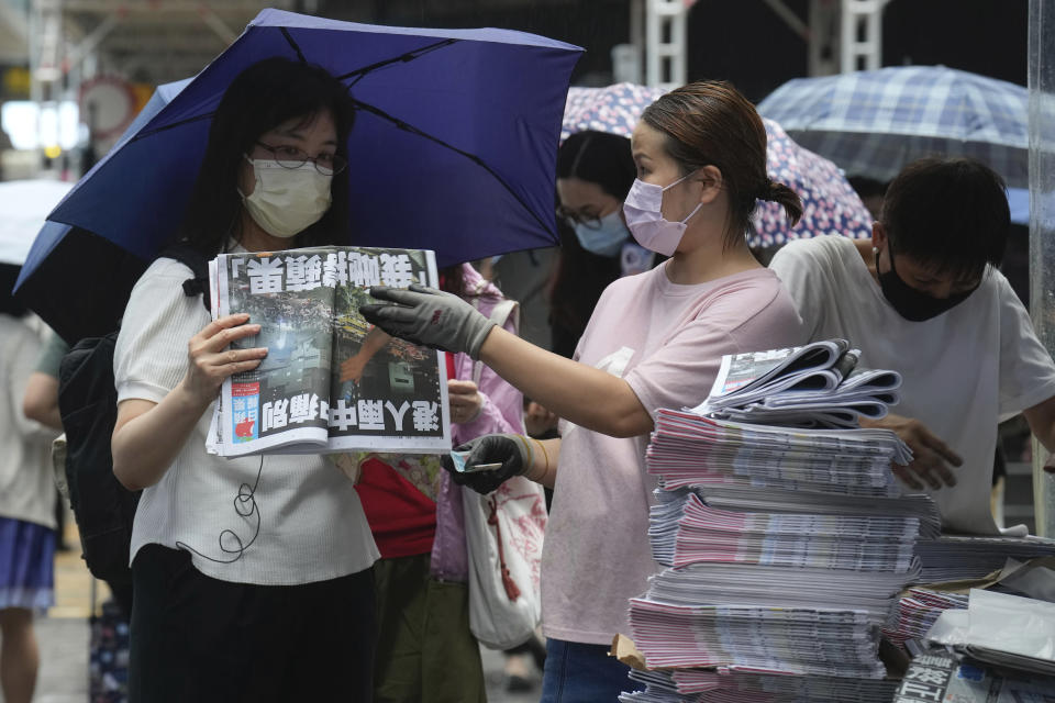 People queue up to buy last issue of Apple Daily at a newspaper booth at a downtown street in Hong Kong, Thursday, June 24, 2021. Hong Kong's sole remaining pro-democracy newspaper has published its last edition. Apple Daily was forced to shut down Thursday after five editors and executives were arrested and millions of dollars in its assets were frozen as part of China's increasing crackdown on dissent in the semi-autonomous city. ( AP Photo/Vincent Yu)