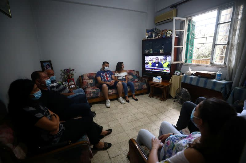 Family members of Ghassan Hasrouty, a missing silo employee, watch a news channel on television as they wait for information, following Tuesday's blast in Beirut's port area