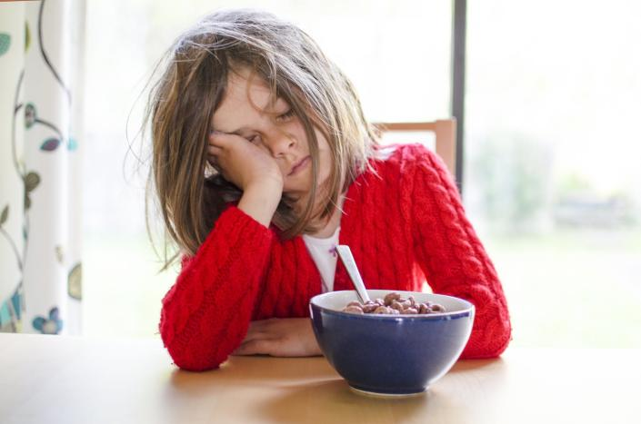 Sleepy young girl at the breakfast table, face in hand.