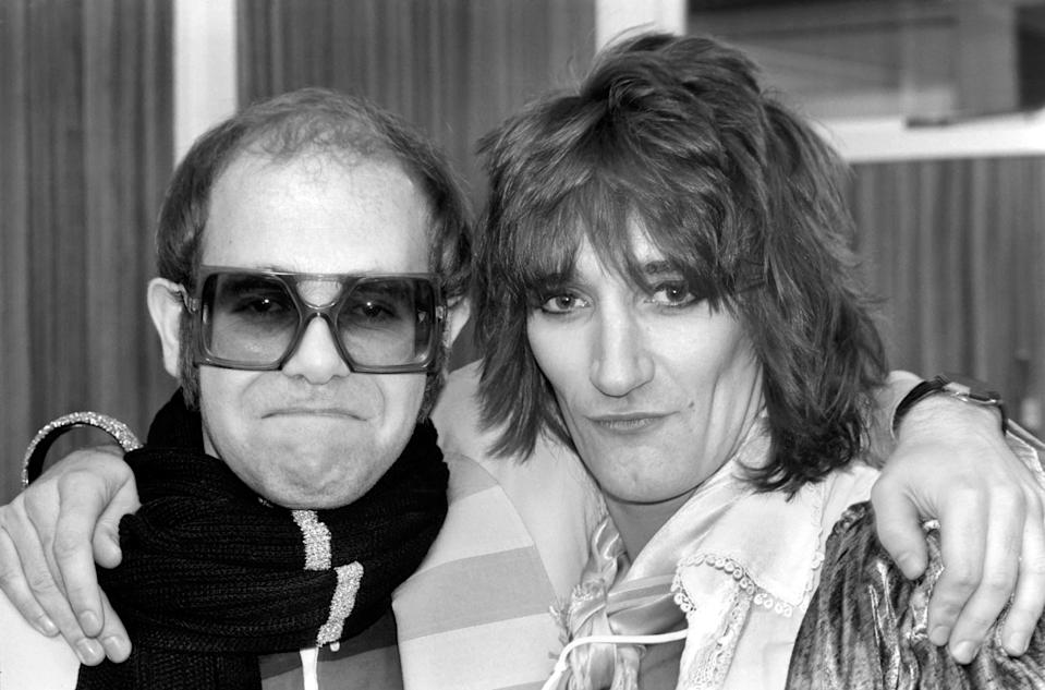 Pop superstars Rod Stewart and Elton John make it up back stage at the Olympic tonight just before Rod went on stage for the third night of his series of London concerts. December 1976 76-07532-001 (Photo by WATFORD/Mirrorpix/Mirrorpix via Getty Images)