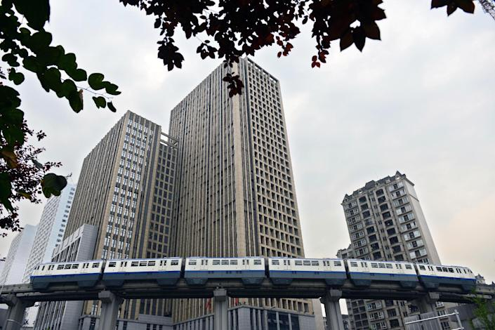 Photo taken on June 24, 2014 shows a train running past residential buildings in southwest China's Chongqing municipality (AFP Photo/)