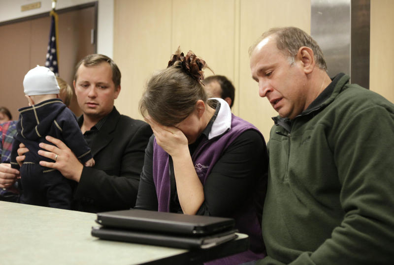 Nadezhada Oliferchik, center, the mother of murder victim Alina Bukhantsov buries her face in her hand as she is comforted by her husband, Vyacheslav, right, during a news conference in Sacramento, Calif, Thursday, Oct. 25, 2012. Denis Bukhanstov, left, discovered his wife, Alina, 23, their daughter, Emmanuela, 3 and son Avenir, 2 murdered when he returned to the family home Tuesday. Their infant son, Mark, 6-months, at left, was found unharmed in another room. Authorities have arrested Denis Bukhanstov's 19-year-old brother, Grigoriy Bukhantsov for the murders. (AP Photo/Rich Pedroncelli)