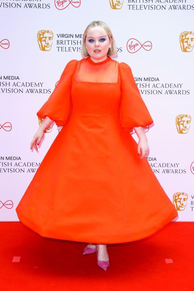 <p>Bridgerton's Nicola Coughlan pulled out all the stops, wearing a bright orange gown by Valentino, which she contrasted perfectly with bright pink heels and blue eyeshadow.</p>