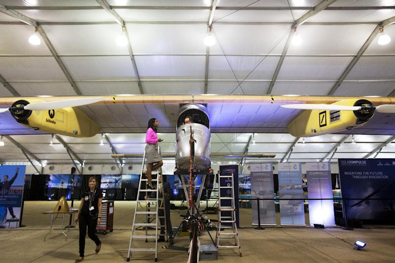 Andre Borschberg, one of two pilots of the Solar Impulse plane is interviewed by a reporter on a ladder as he sits inside the cockpit of the solar powered plane during a media availability at the Smithsonian National Air and Space Museum's Steven F. Udvar-Hazy Center at Washington Dulles International Airport in Chantilly, Va., Monday, June 17, 2013. (AP Photo/Jacquelyn Martin)